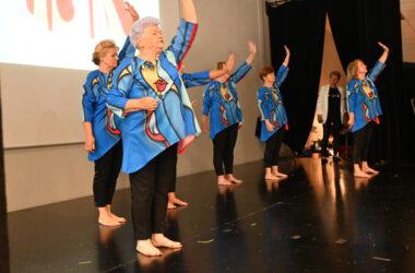 Sześć seniorek tańczy w niebiesko czarnych strojach.