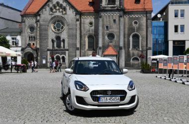 Biały samochód Suzuki Swift na tle kościoła Ewangelickiego na Rynku w Tarnowskich Górach