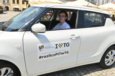 Laureat Pan Tymon w wygranym białym samochodzie Suzuki Swift