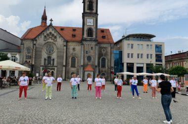 Grupa seniorek tańczących na Rynku w kolorowych strojach, w tle kościół Ewangelicki.