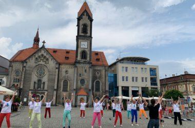 Grupa seniorek tańczących na Rynku z rękami podniesionymi w górę, w tle Kościół Ewangelicki.