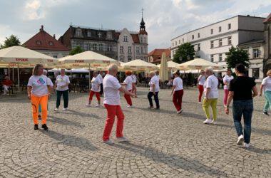 Grupa seniorek tańczących na Rynku w kolorowych strojach, w tle tarnogórski Rynek.