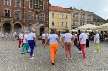 Grupa seniorek tańczących na Rynku, w tle tarnogórski Ratusz i kamienice.