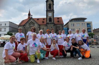 Szesnaście seniorek z UTW z Marzeną Kobryń i Eweliną Pankiewicz w tle Kościół Ewangelicki na rynku