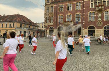 Grupa seniorek tańczących na Rynku, w tle tarnogórski Ratusz.