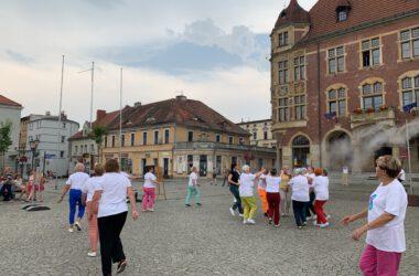 Grupa seniorek tańczących na Rynku w kolorowych strojach, w tle tarnogórski Ratusz.