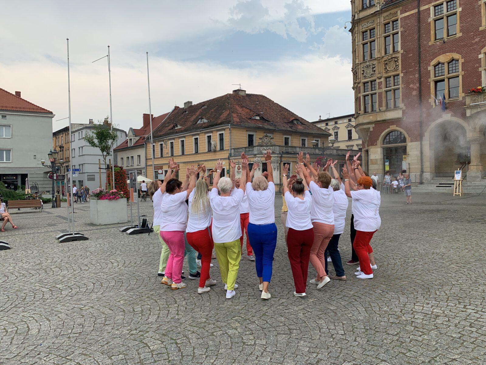 Grupa seniorek tańczących na Rynku z rękami podniesionymi w górę, w tle tarnogórski Ratusz.