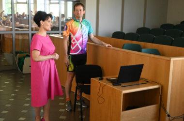 Kobieta w różowej sukience i mężczyzna w sportowym stroju w sali konferencyjnej.