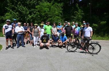 Grupa rowerzystów w parku z Burmistrzem Arkadiuszem Czechem