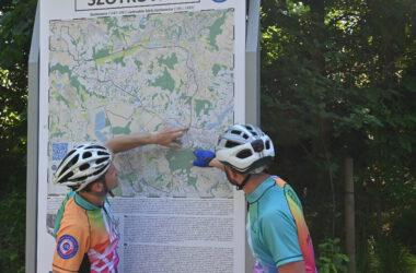 Dwóch rowerzystów patrzących na mapę w parku