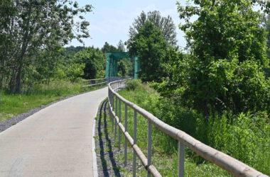 Ścieżka rowerowa wśród zieleni z zielonym metalowym mostem w tle.