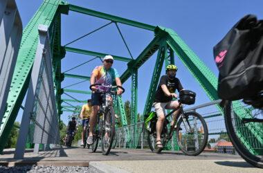 Grupa rowerzystów przejeżdżających ścieżką rowerową po zielonym metalowym moście.