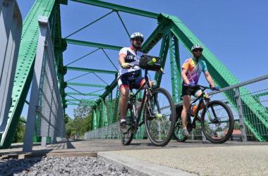 Dwóch rowerzystów przejeżdżających ścieżką rowerową po zielonym metalowym moście.