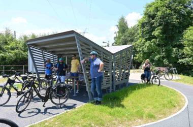 Grupa rowerzystów przy wiacie rowerowej