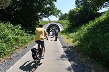 Grupa rowerzystów wjeżdżających w tunel pośród zieleni