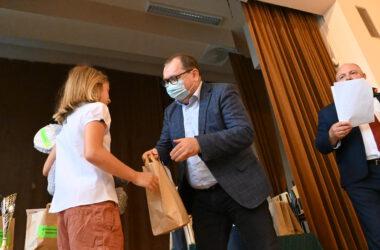 Dziewczynka przyjmująca nagrodę z rąk Pana Andrzeja Pilota.
