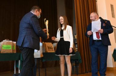Uczennica przyjmująca puchar z rąk Pana Andrzeja Pilota.