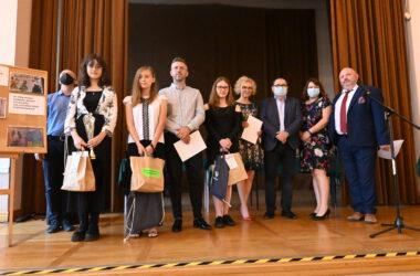 Trzy uczennice i jeden uczeń na scenie z dyplomami, nagrodami, organizatorami i sponsorami konkursu.