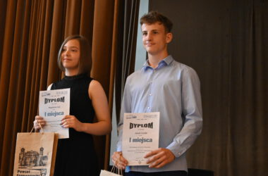 Uczennica i uczeń z dyplomami i nagrodami.