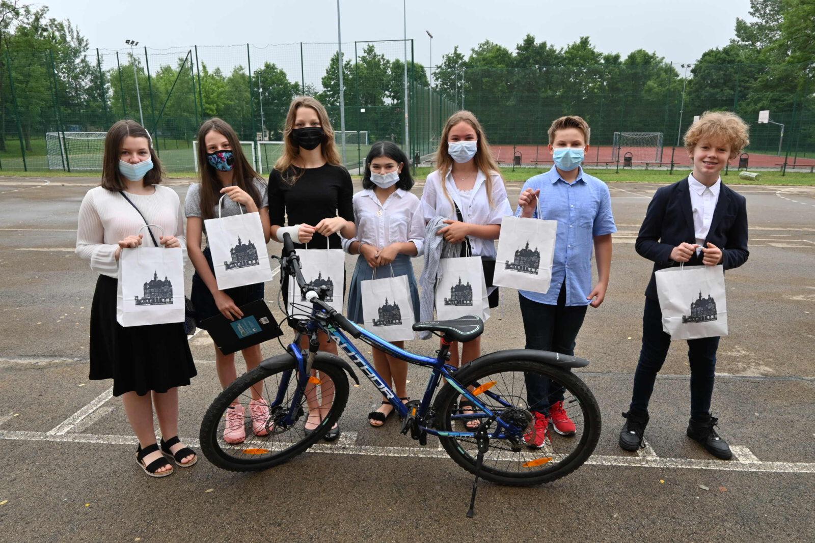 Pięć dziewczynek i dwóch chłopców z prezentami w tarnogórskich papierowych torbach a przed nimi rower