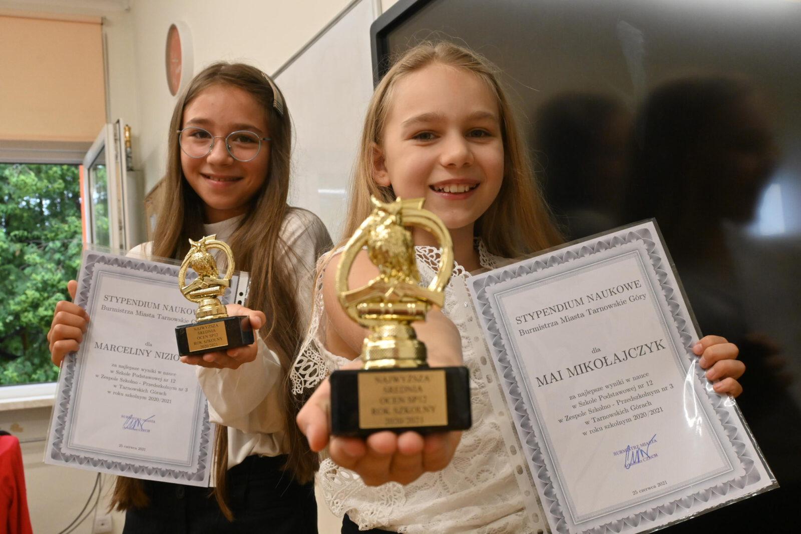 Dwie uśmiechnięte dziewczynki z dyplomami i statuetkami w dłoniach.