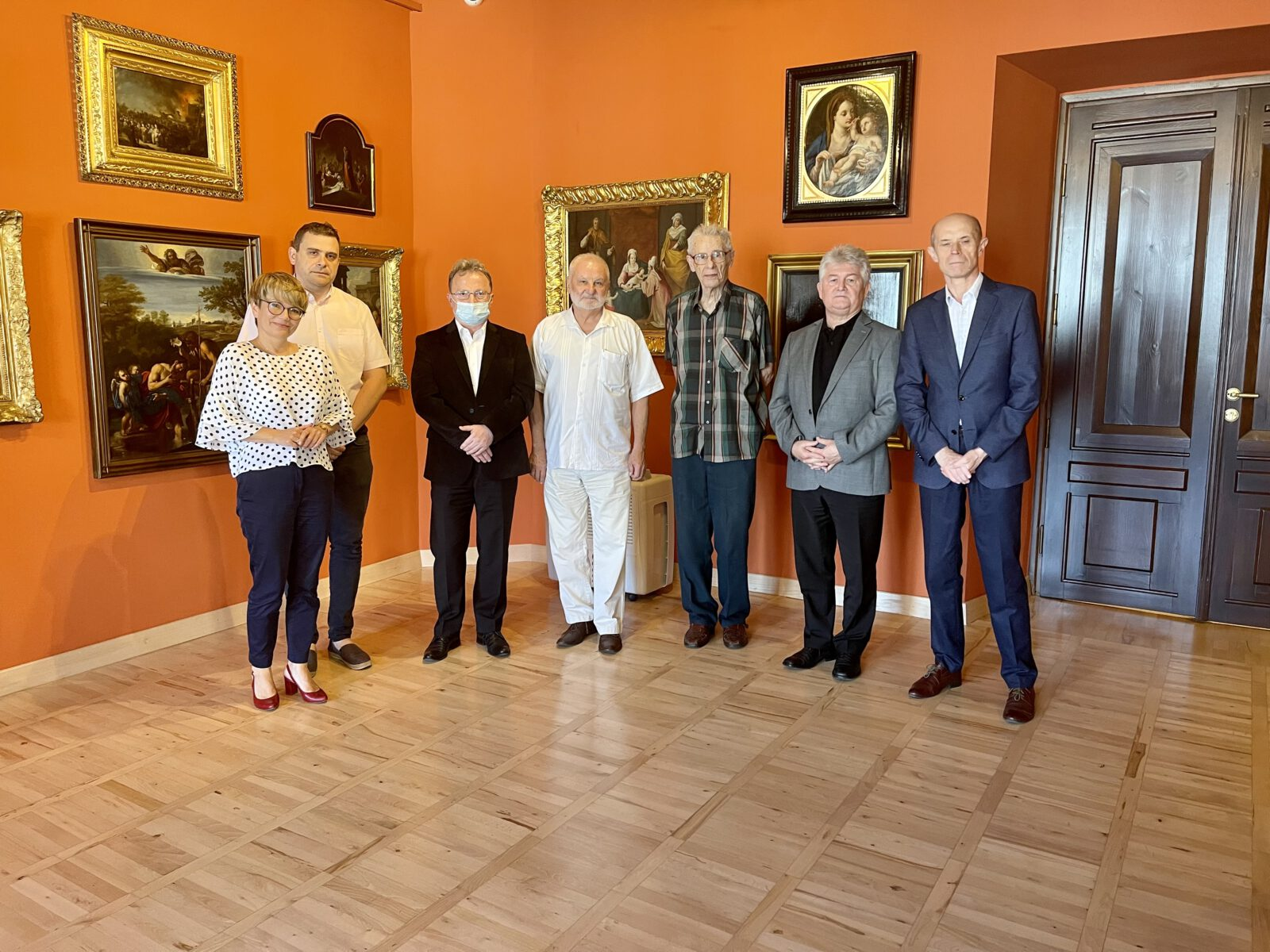 Siedem osób z rady Muzeum na tle obrazów.