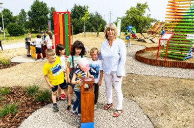 Pani Jolanta Tuszyńska z piątką dzieci bawiących się na placu zabaw mBanku w Starych Tarnowicach.