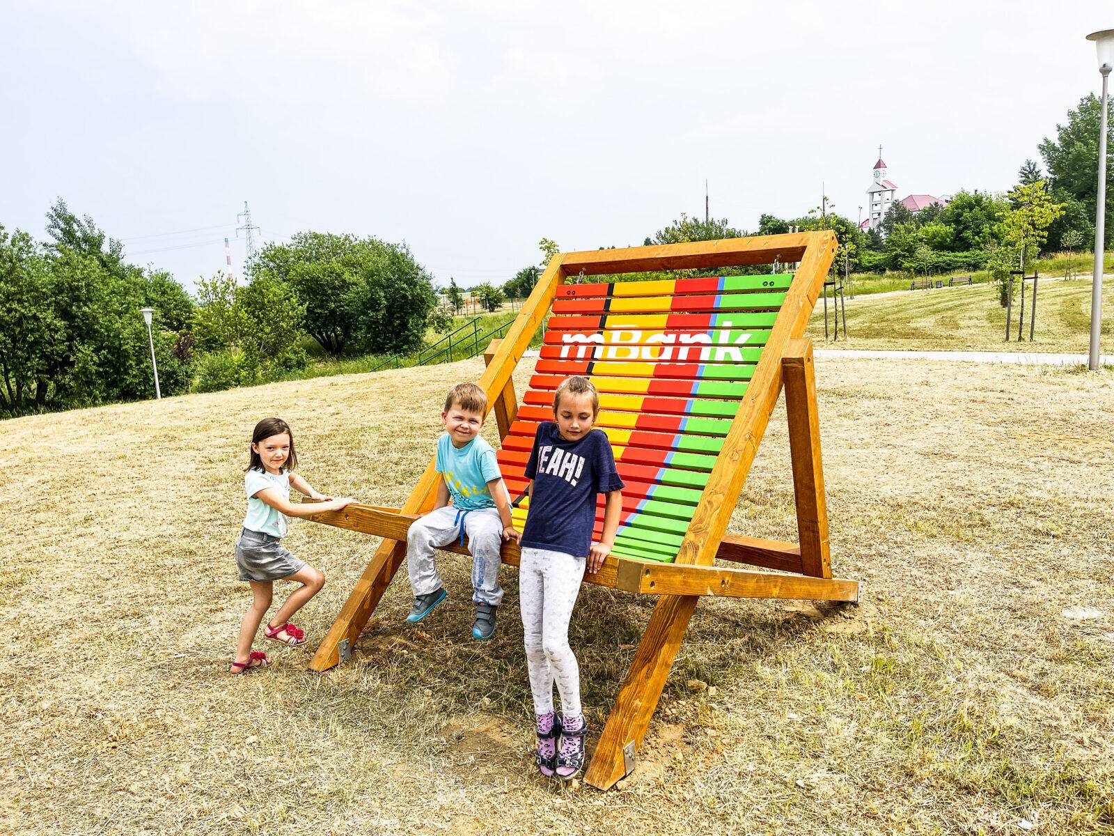 Dziewczynka i dwóch chłopców na placu zabaw mBanku przy ogromnym kolorowym leżaku
