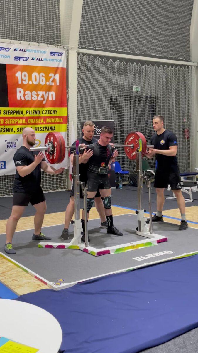 Radosław Dębicki ze sztangą w asyście trzech mężczyzn na zawodach
