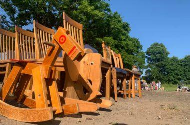 Drewniany koń i słoń na biegunach oraz kilka drewnianych krzeseł na tle drzew