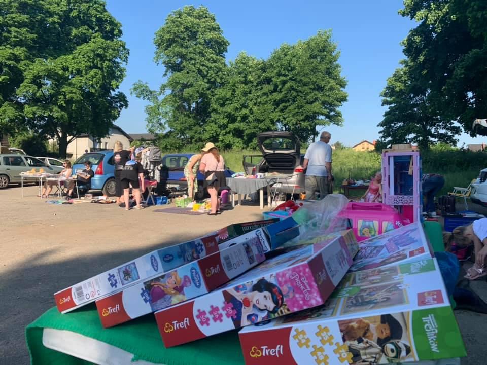 Stoisko targowe z puzzlami dla dzieci, w tle drzewa ludzie i zaparkowane samochody
