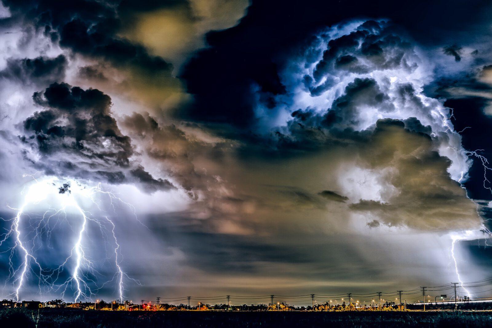 Burzowe ciemne niebo z kłębiastymi chmurami i błyskawicami.