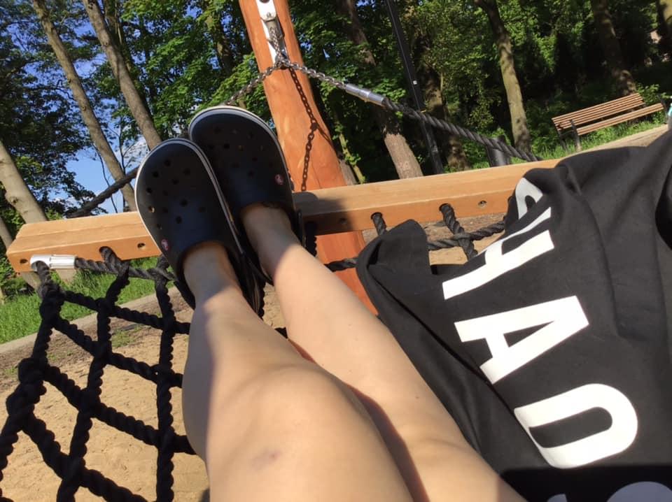 Damskie nogi na hamaku na tle drzew.