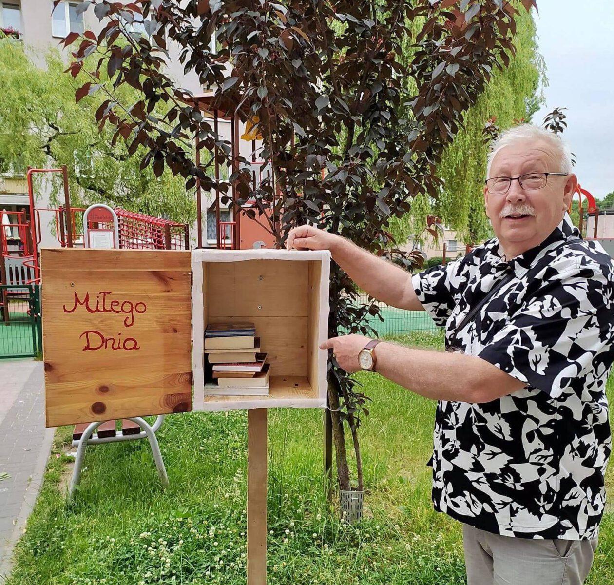 Przewodniczący Rady Dzielnicy Osada Jana - Stefan Wrodarczyk z drewnianą skrzynką z książkami w środku..