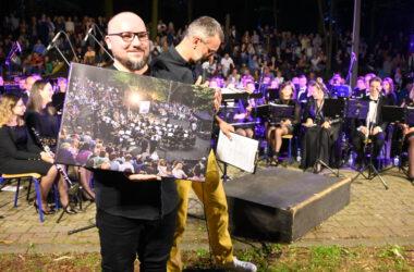 Aleksander König na tle orkiestry z fotografią w rękach