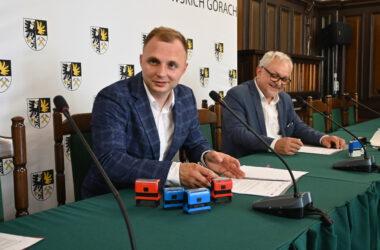Burmistrz Tarnowskich Gór Arkadiusz Czech przy stole z zielonym obrusem z przedstawicielem firmy .