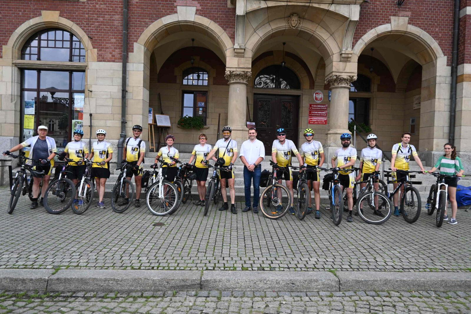 14 osób z rowerami w koszulkach z herbem Tarnowskich Gór na tle Ratusza.