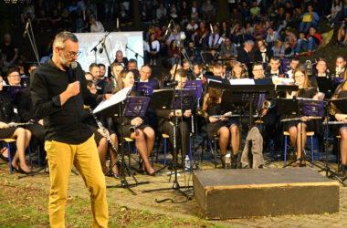 Mariusz Jarzombek zapowiadający kolejny utwór na tle orkiestry
