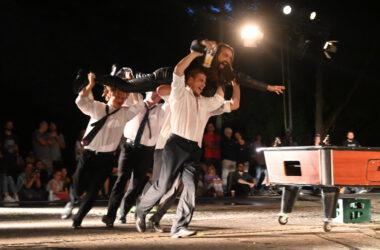 4 mężczyzn w białych koszulach. Biegną trzymając w górze mężczyznę w czarnym stroju z kuflem piwa w dłoni. Z prawej strony stół bilardowy.