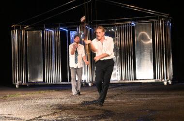 2 mężczyzn w białych koszulach. Żąglują kulami bilardowymi. W tle metalowa scenografia.