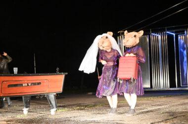 2 Aktorki przebrane za myszy w fioletowych sukienkach. Jedna w białym welonie. Druga trzyma w ręce czerwoną walizkę na kółkach. Z lewej strony stół bilardowy.