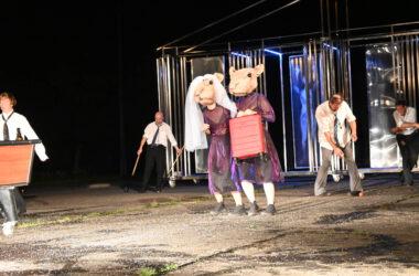2 Aktorki przebrane za myszy w fioletowych sukienkach. Jedna w białym welonie. Druga trzyma w ręce czerwoną walizkę na kółkach. W tle metalowa scenografia i 4 mężczyzn w białych koszulach.