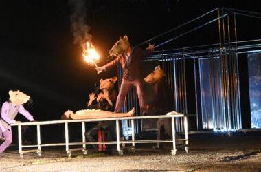 Naga kobieta na stole i 4 aktorów przebranych za myszy. Jeden trzyma rozpalony świecznik i stoi na stole.