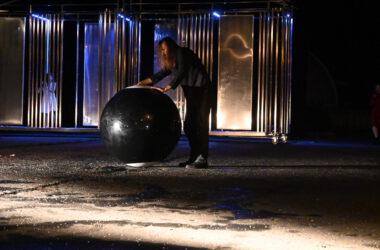 Aktor z ogromną kulą bilardową na tle metalowej scenografii.