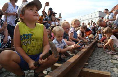 Grupa dzecie na tarnogórskim rynku uderza młotkami w szynę kolejową.