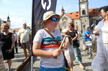 Chłopiec w czapce i w przeciwsłonecznych okularach z młotkiem w ręce. W tle kościół ewangelicki.