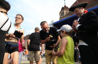Mężczyzna z mikrofonem na tle sceny przed ratuszem zadaje pytanie chłopcu z młotkiem. Z prawej strony mężczyzna w stroju Napoleona.
