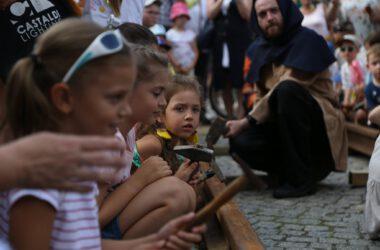 Dziewczynki z młotkami przy szynie kolejowej na tarnogórskim rynku. W tle mężczyzna z młotkiem w stroju gwarka.