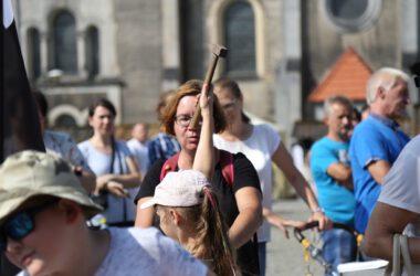 Na pierwszym planie dziewczynka odwrócona tyłem z młotkiem w górze. W tle kościół ewangelicki.