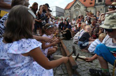 Grupa dzieci na tarnogórskim rynku uderza młotkami w szynę kolejową. W tle kościół ewangelicki.